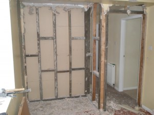 Plasterboard removed from one side of the partition showing the wooden stud work