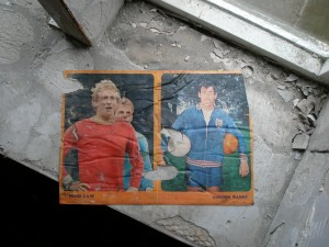Football stars from the 1970s pasted to the wall behind the partition.