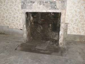 The original fireplace revealed.  The two sides are stone slabs on end.  The top is a stone slab laid vertical between them.  The hearth is made up of flagstones.  Like the rest of the floor, although much of it has been covered up with a sort of asphalt material.  Presumably, to keep the damp out.
