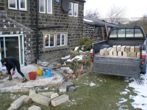 We reversed the pickup onto the back garden and used it to remove the rubble from the base of the conservatory.  We stacked the old stone (shown in the back of the truck), but the material from the inside wall went into the skip.  We simply reversed the truck up to the skip and threw it in.  Simples.