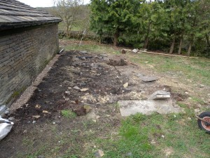 This is the site of the old chicken shed, just behind the re-roofed outbuilding.  The large slab in the front of the camera is the step into the chicken shed.  We will reuse this with the polytunnel.