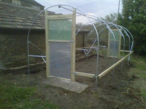 The timber rail is where the polythene is attached.  This rail can be moved down the hoops in order to tension the cover.