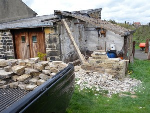 The lean-to is taken down stone-by-stone.  Each of the stone is cleaned and then stacked in the back of the pickup.