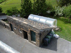 This is the outbuilding (with new roof) and the newly installed polytunnel.  The orchard is behind.