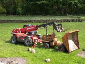 The telehandler is used to reach up to roof level with a pallet.  This is then loaded with slates and brought down to ground level while the roof is being repaired.