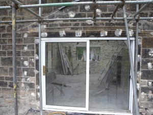 The date stone is on the lintel to the left of the sliding doors.