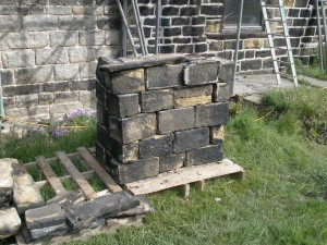 The stones from the old chimney have been cleaned and stacked on a pallet ready to go back up.