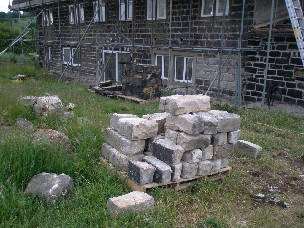The stone for the chimenys is stacked on pallets ready to be rebuilt.  Zep is in the background looking for any leftover coleslaw!  Blame the builders!