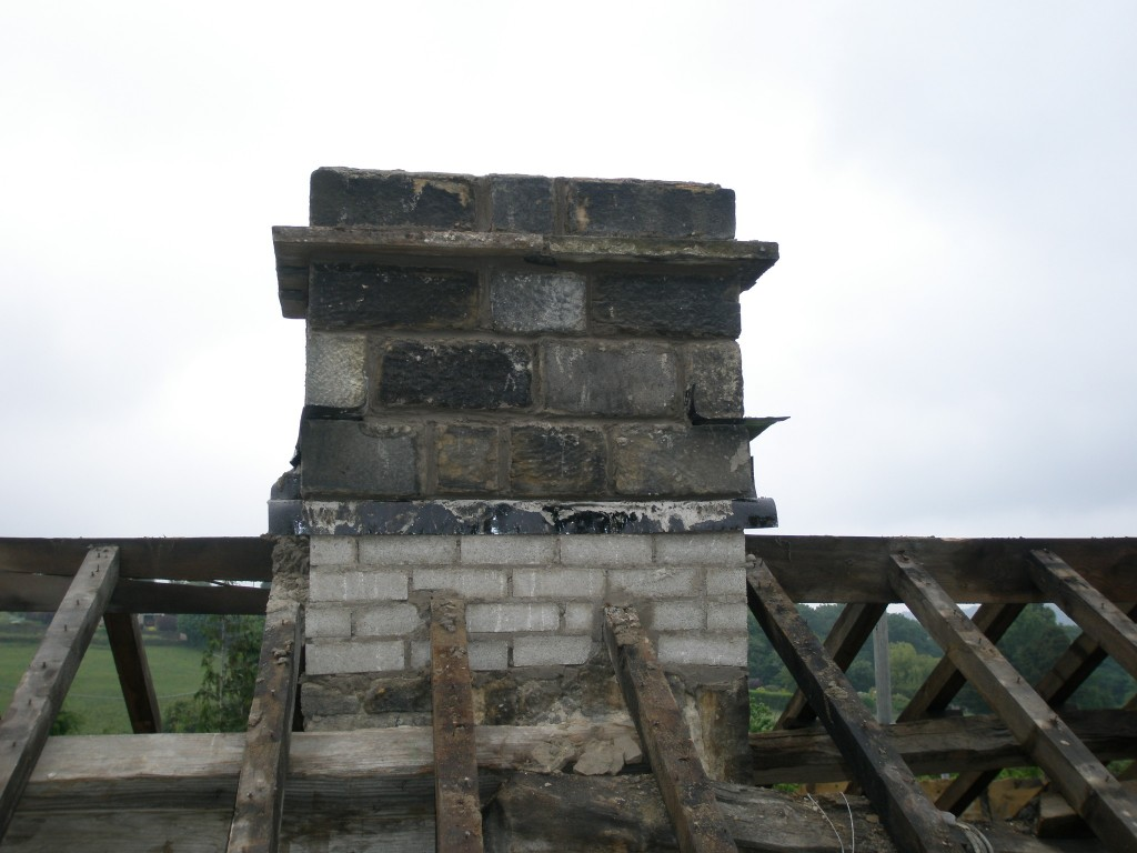 Using the stone from the porch, the chimney between number 10 and number 9 has been rebuilt.  An old flagstone was cut to make up the string course.
