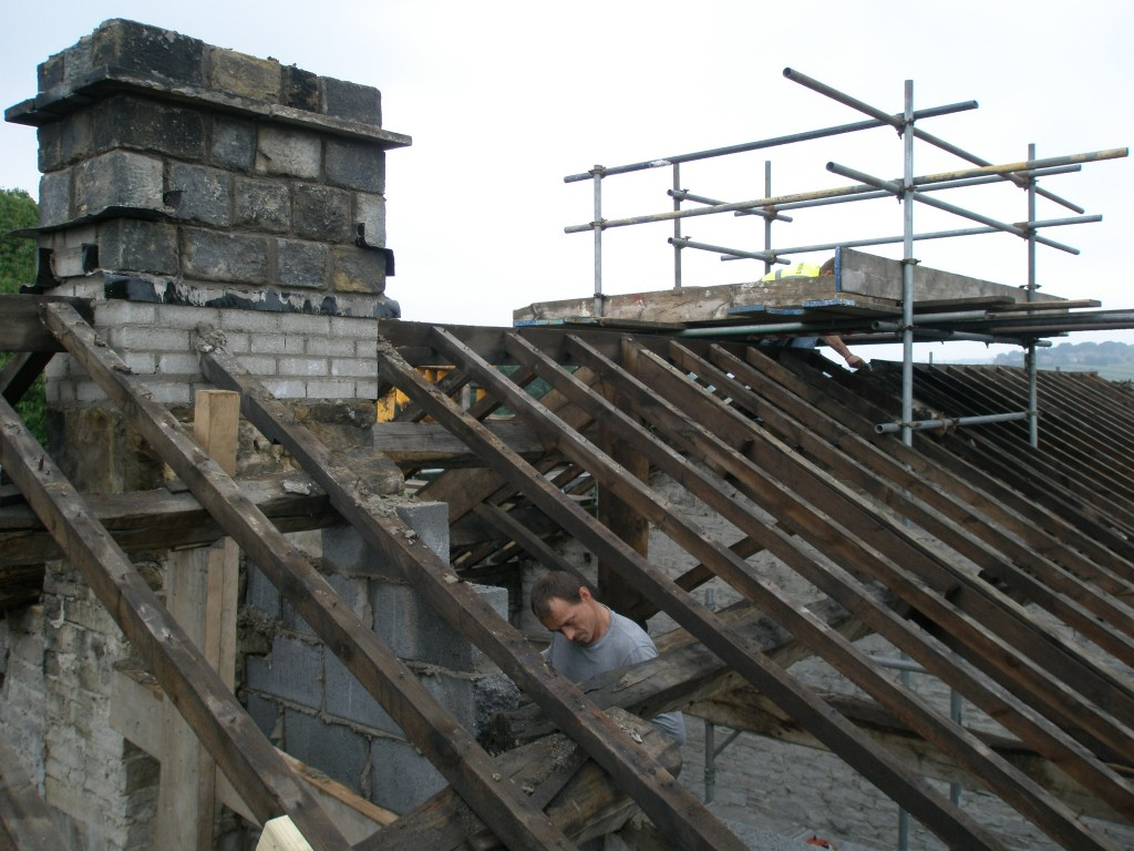 The first chimney is rebuilt and work is starting on the second one.  Andy is putting one of the purlins back in.