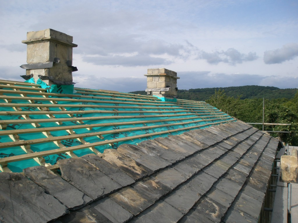 Five courses of slates on the back of the roof and the two re-built chimneys. This is day 3 for putting the roof back on.