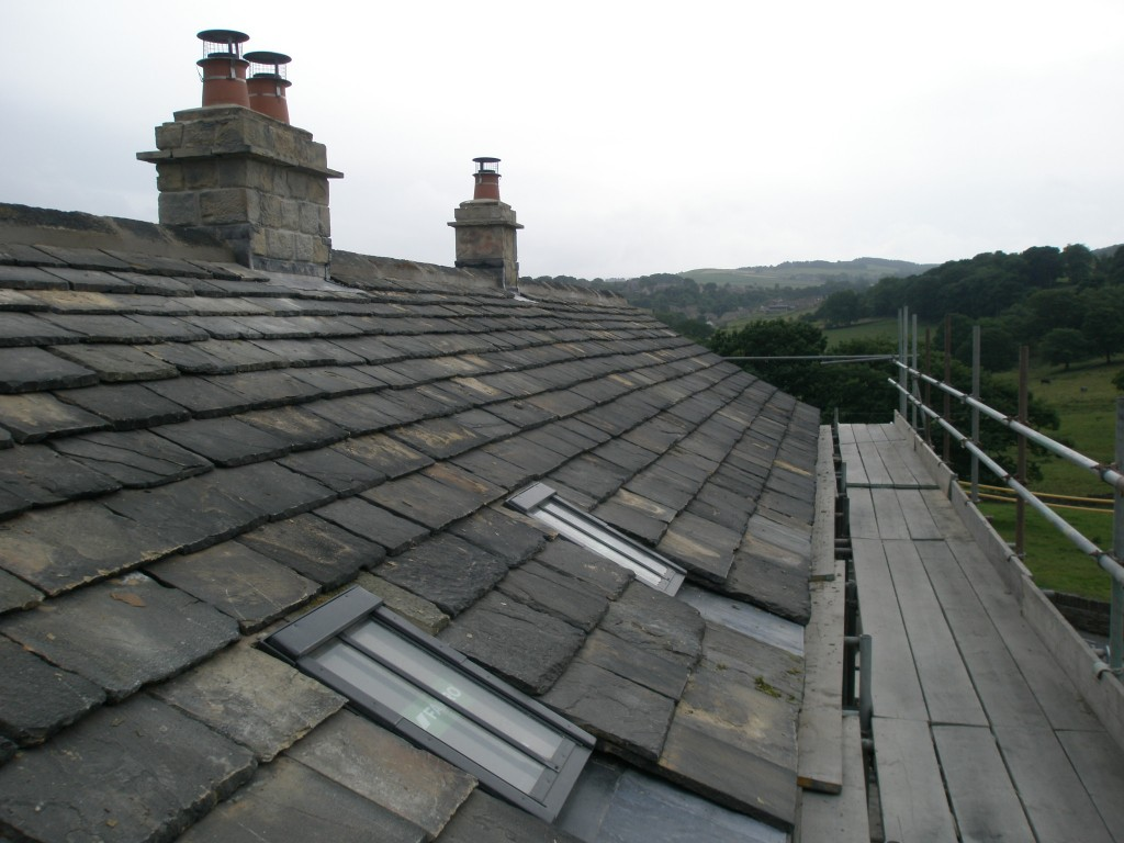 The front of the main roof of the existing cottages.  Two rebuilt chimneys (complete with flues and pots) and two new roof lights.