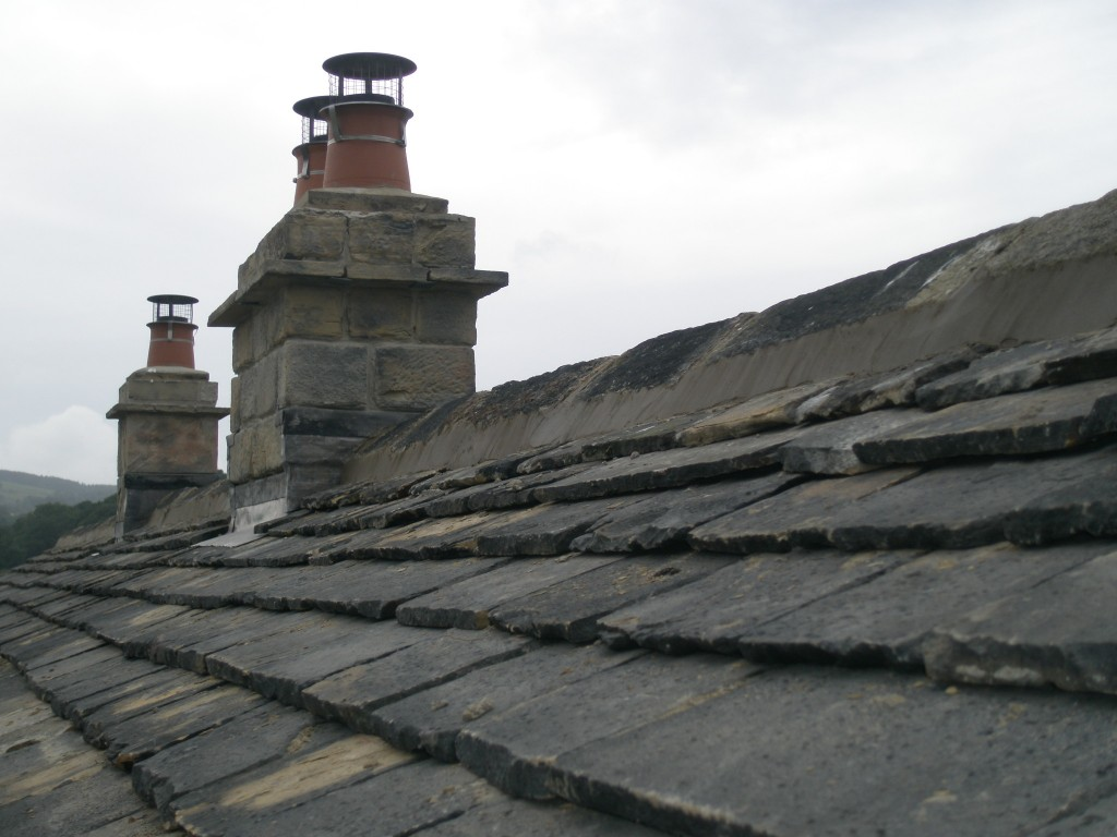 Rebuilt chimneys and pointed ridge tiles on the back of the roof