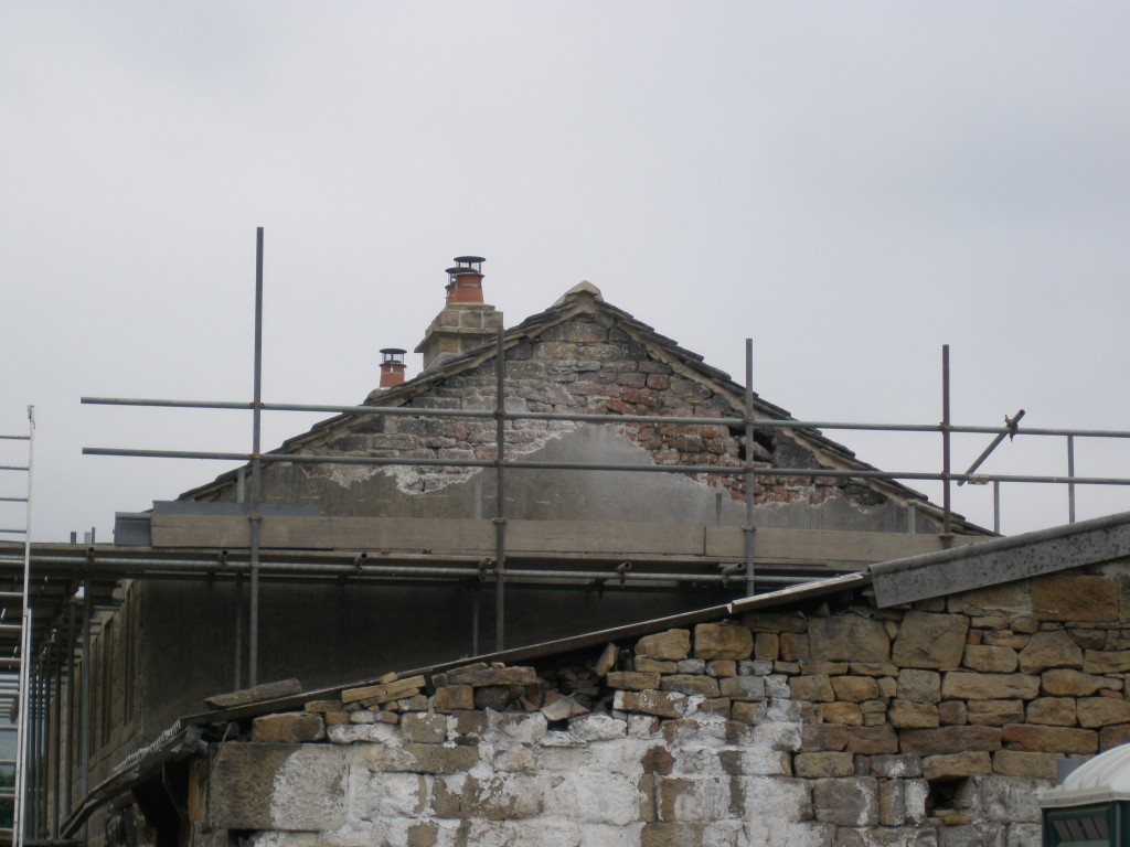 The roof line of the new extension is going to be lower than the existing roofline.  This means that part of the gable end (that is currently rendered) is going to be exposed.  We need to remove the rendering to check the quality of the underlying stone.