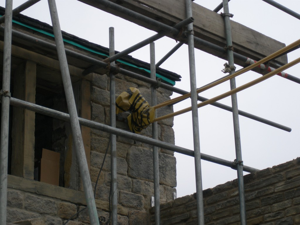 The existing electricity supply comes in via overhead cables.  The cables are then attached to the front of the house. The plan is that there will be put underground and brought round into the new extension.  The yellow sheaths are to protect the guys working on the scaffolding.