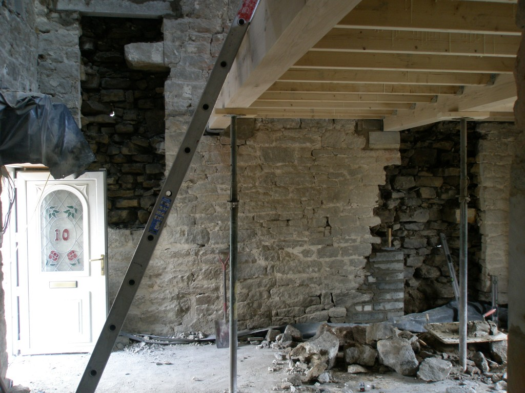 The opening on the right is the door from the hall into the kitchen (or at least it will be!).  The opening on the left is a large internal window between hall and kitchen.  What you can see here is the back of the outer set of stones that makes up the wall.