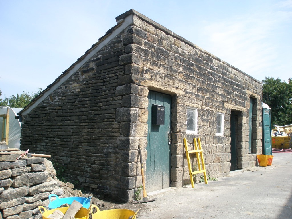 The outbuildings before being sandblasted.  I have had to remove the small wall here to make sure that we can get to all of the side wall.