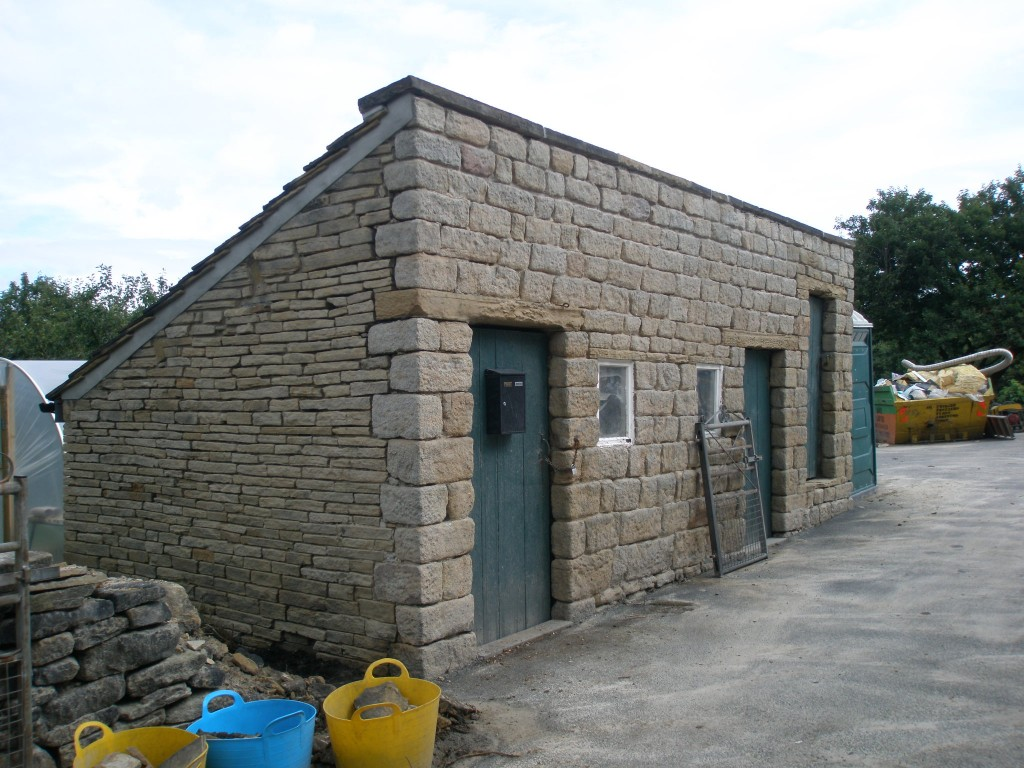 The outbuildings after they had been sandblasted.  They now need to be pointed to make them fit in with the rest of the buildings.