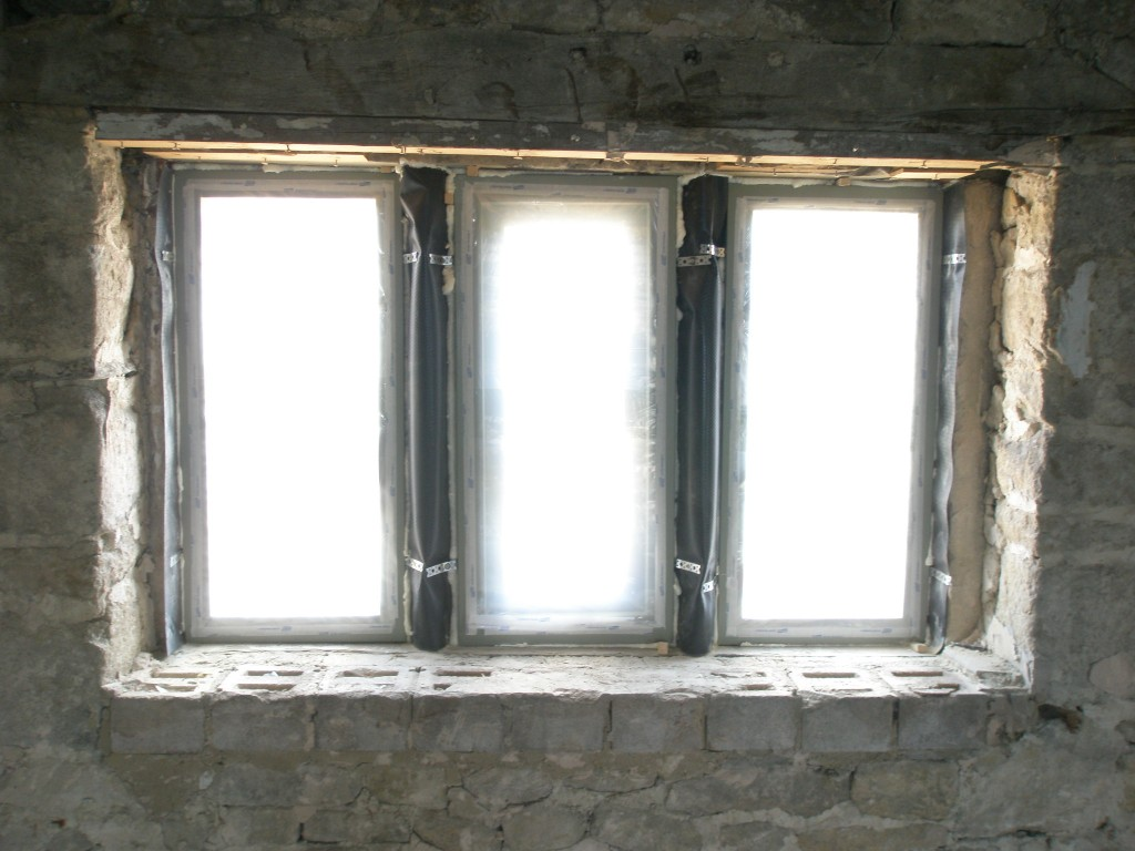 Now all of the windows are in, we have covered the insides with a lightweight plastic to protect them while the inside is being plastered.  The windows were installed with the final coat of paint already on.