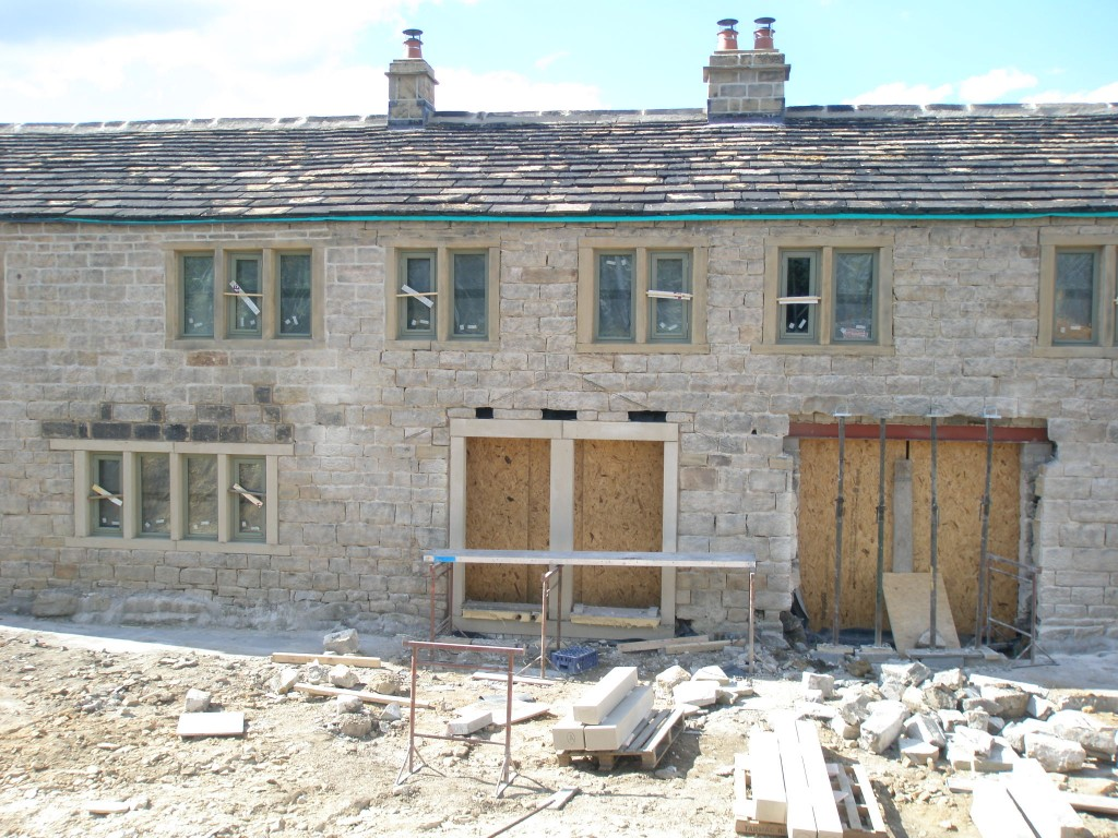 We have now replaced the ashlar above the window to the left.  The window head is now the same thickness as the other windows, but the stones that have been used to wall it up need to be sandblasted.  There are two pairs of doors at the rear and the stone surround for the first of them has gone in.