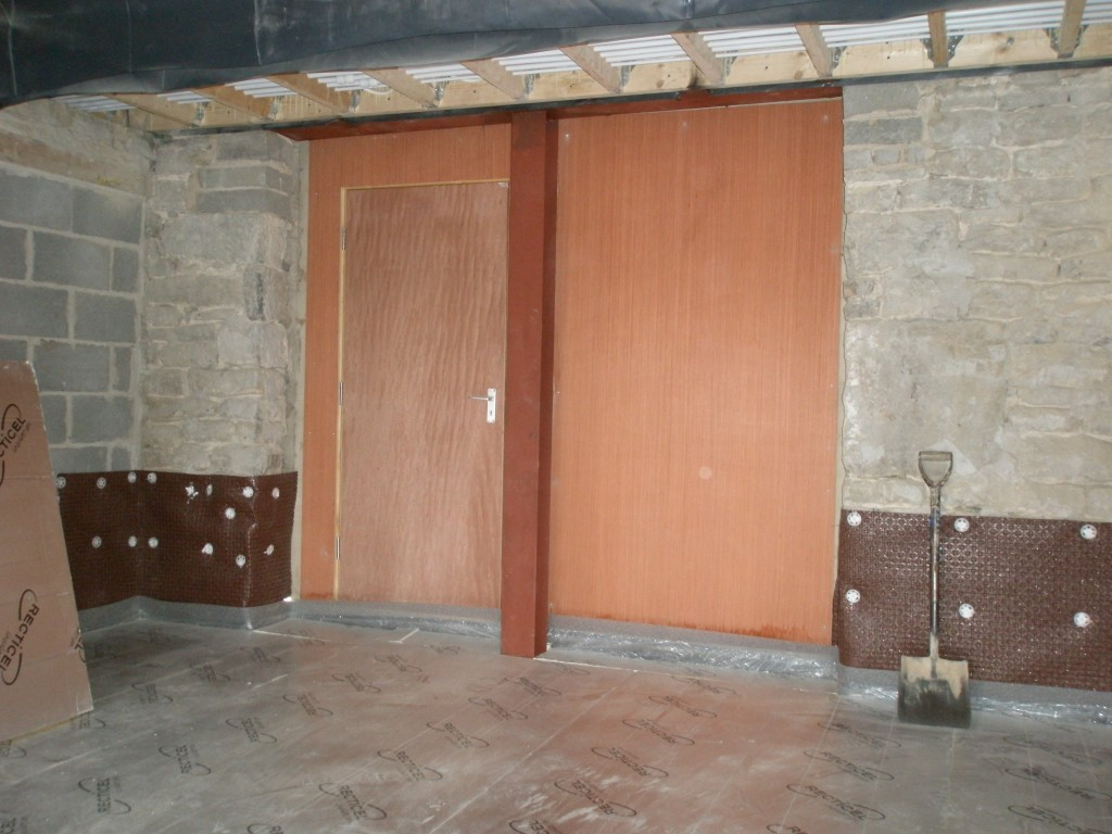 """The insulation is down on the floor.  The damproof membrane has been fixed to the walls.  There will be two large doors here that open on to the courtyard, but for now we have boarded one up and put a temporary door on the other.  If we put the """"real"""" doors on now, they would only get damaged during the building work."""