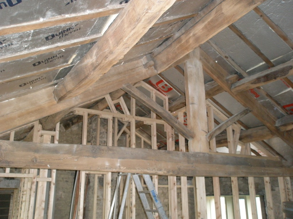 The roof insulation consists of 50mm high density boards that are foil coated on either side.  This are cut and fitted between the rafters.  They are then covered by a insulatied plasterboard before being finally plastered.