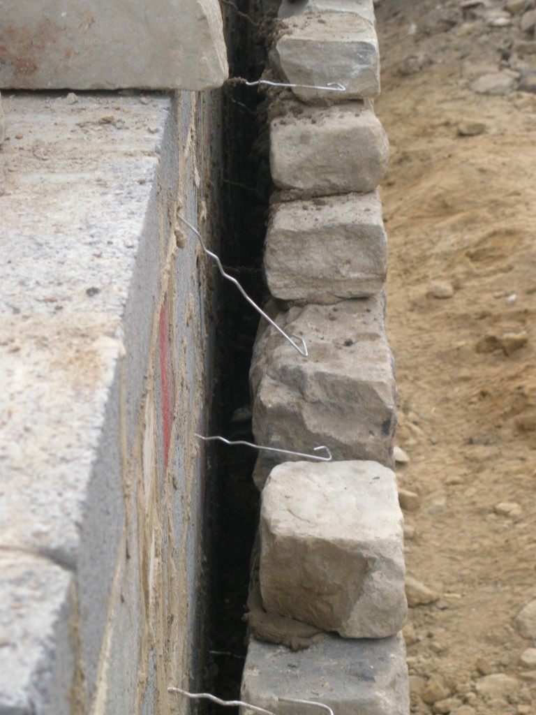 This shows how the reclaimed stone wall has been tied into the retaining block wall.  The ties are made of stainless steel.