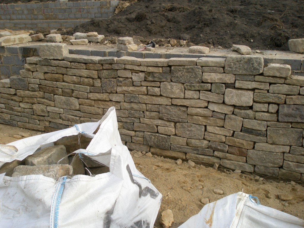 "The wall is made of reclaimed stone.  We are using two sizes of stones 3 - 3.5 and 6 - 6.5.  The larger stones are used as ""jumpers"" to break up the courses and make it less uniform."