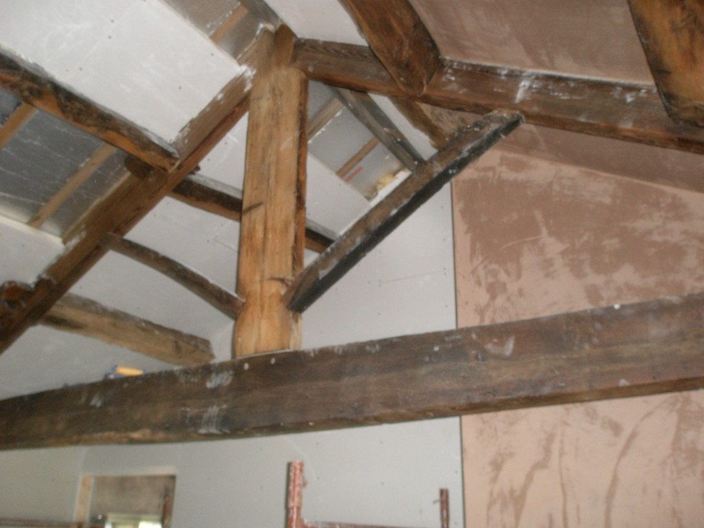 The rafters are hidden underneath the insulated plasterboard, but the roof trusses and purlins will remain exposed.  The exposed timber has been waxed and it should be easy to get off any dust or plaster marks.