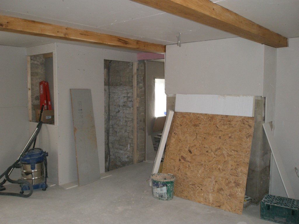 This is the downstairs bedroom in the existing cottages.  We will plaster around the fireplace.  We have boarded around the cellar steps and created a cupboard for the lighting computer (just above the vacuum cleaner).