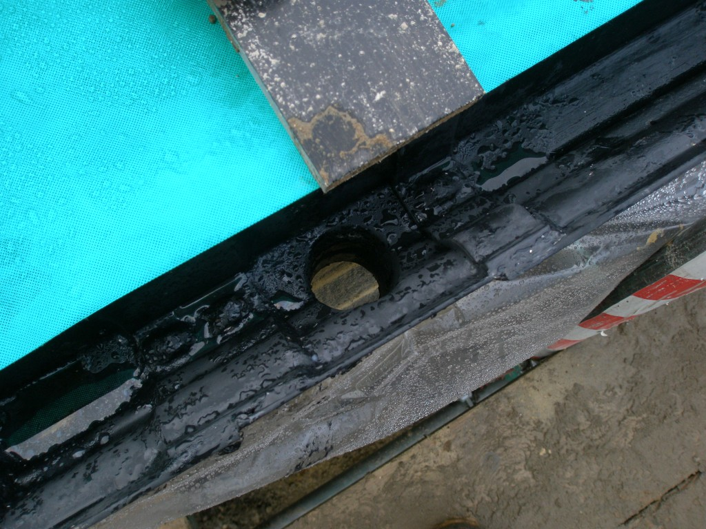 The ashlar shelf has had to be core drilled to accomodate the rain water down pipe.