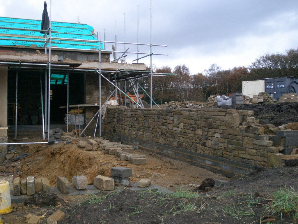 The top wall in the sunken garden is nearing completion.  We are expecting the coping stones sometime this week, so it will be good to see them go on.