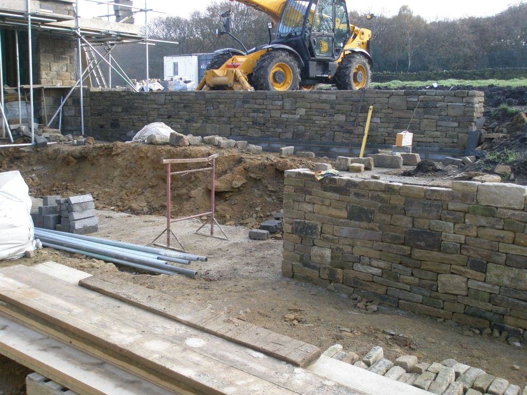 Despite some pretty wet and muddy conditions, the upper terrace wall is now ready for coping stones.