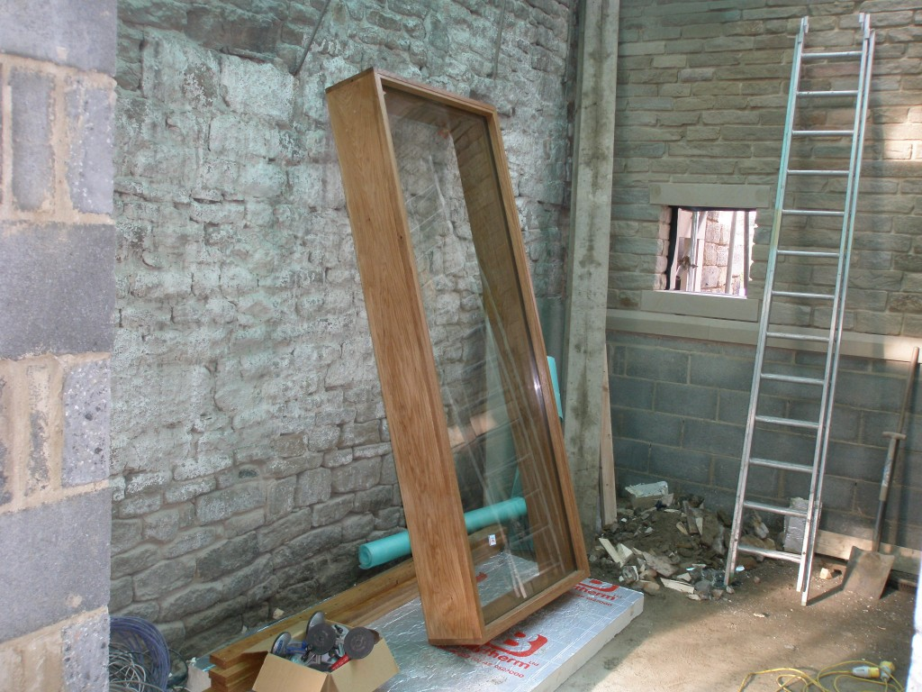 This is the smaller of the two oak frame windows.  This one arrived on site fully glazed.  The wide part of the frame sits on the outside of the building.