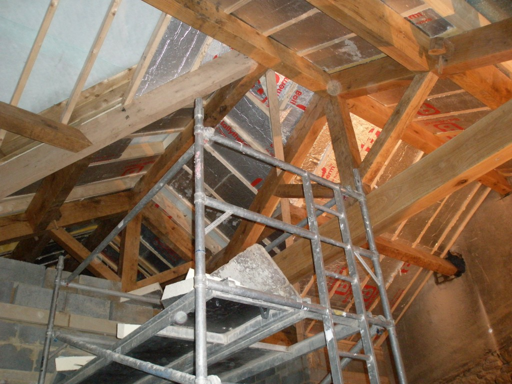 We are putting 100mm insulated boards between the rafters in the new extension.  This is then covered with insulated plasterboard.  This will leave the oak trusses exposed.  Because the ceiling is so high, this has to be completed using tower scaffold inside the building as ladders will not reach.