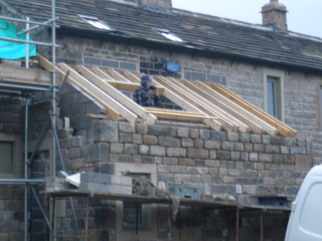 The roof finally went on the porch today.  This is Andy the Joiner doing a fine impression of a tank commander while have a cup of coffee!