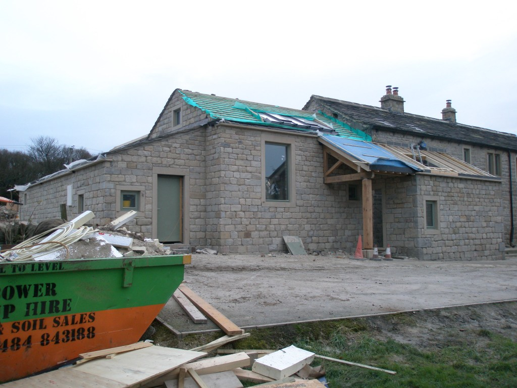 The stonework on the new extension and porch were sandblasted today.  This effectively removes a loose dirt or paint from the surface of the stone.  By the time that it is pointed, it will be close match to the existing cottages.  The roof of the porch and kitchen will be finished off next week.
