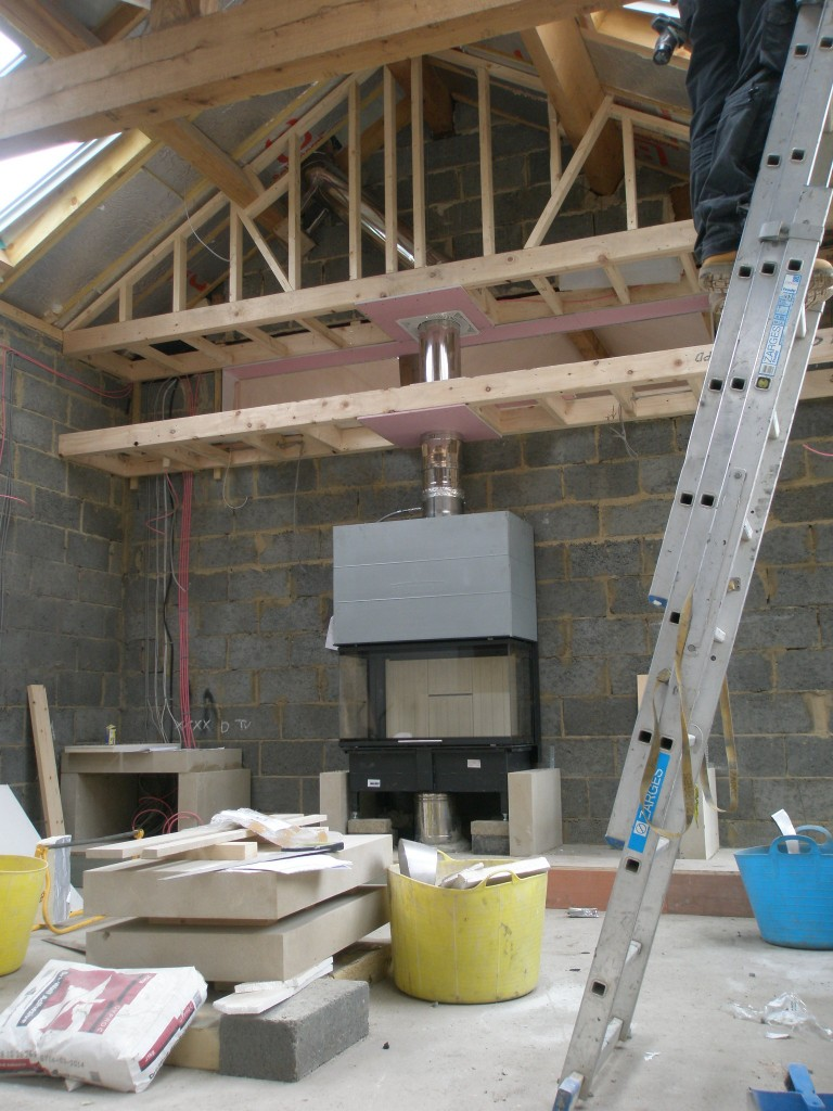 "The Spartherm unit is now installed, although the chimney breasy still needs to be formed around it.  The studwork that meets the roof line is there to mask the fact that the flue has a ""dog leg"" to avoid the large ridge beam.  This is a big flue - 8 inches in diameter."