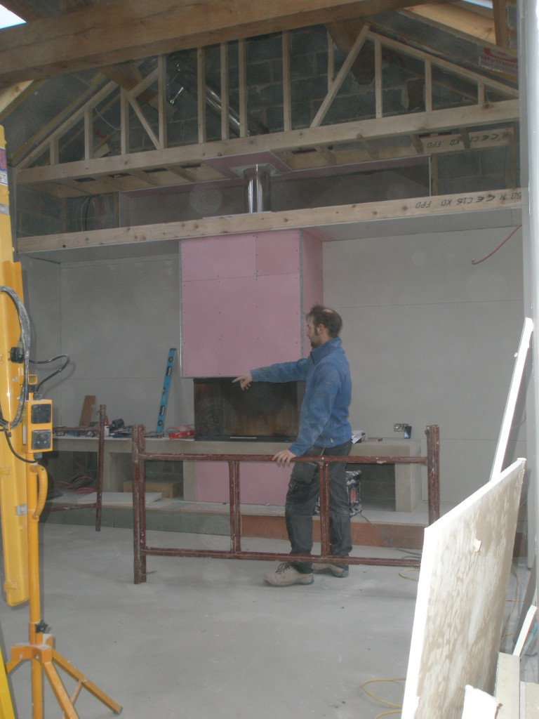 The pink plasterboard is fireline board.  This is more resistant to heat than normal plasterboard and makes it ideal for using around a fireplace.