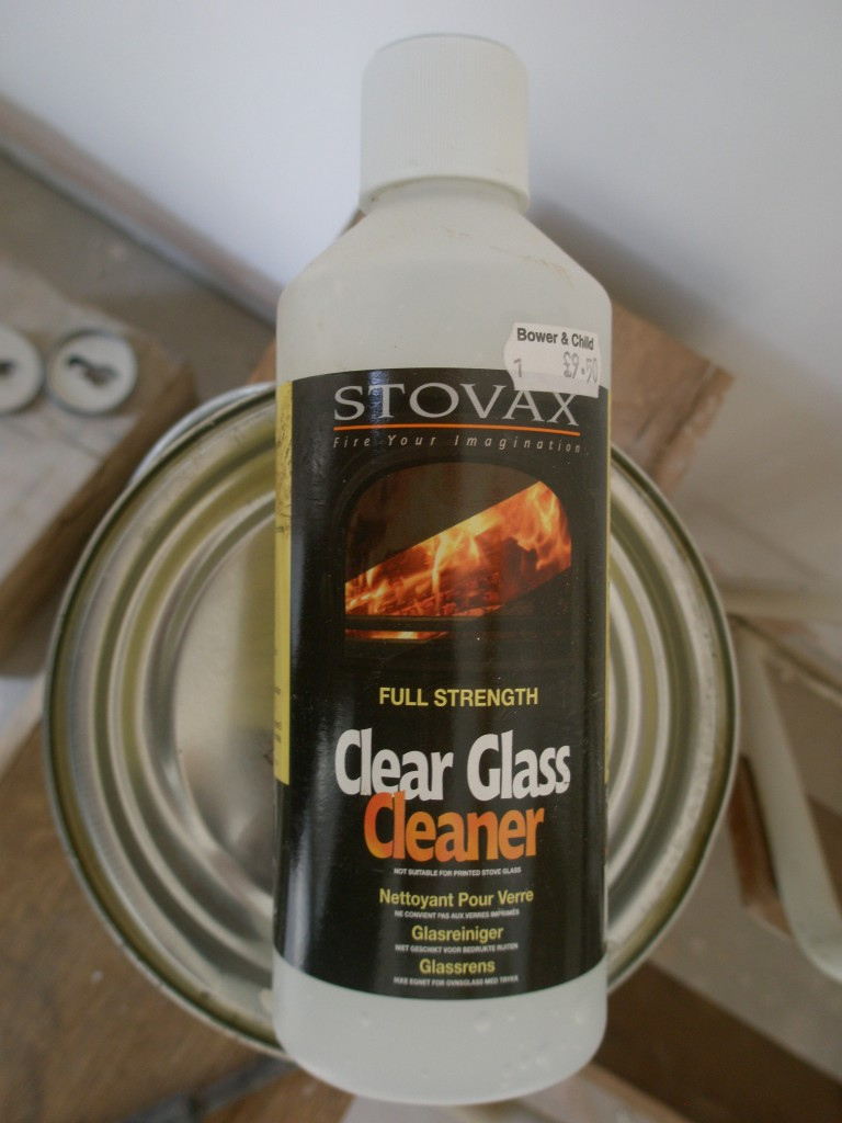Stovax glass cleaner.  This works a treat.  It is caustic so be careful when you use it.  It says to apply it liberally and leave it for 5 minutes before removing with a damp cloth.  I use it sparingly and clean off within a minute or so.  It is expensive, but you don't need to use much of it.