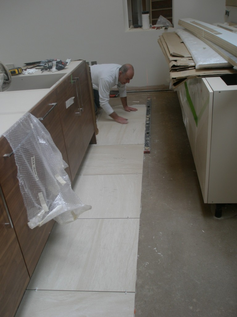 The first of the tiles are going down on the kitchen floor.  It took John a couple of hours to work out the best way of laying the tiles.