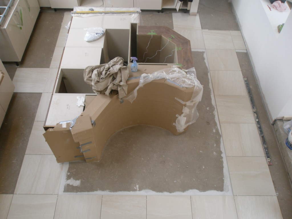 End of day 1 and we now have a square of tiles right around the island unit.  This is the quick bit.  Next are the cut tiless that go around the edge of the kitchen.  However, tomorrow it will be possible to walk on these tiles to access all of the kitchen.