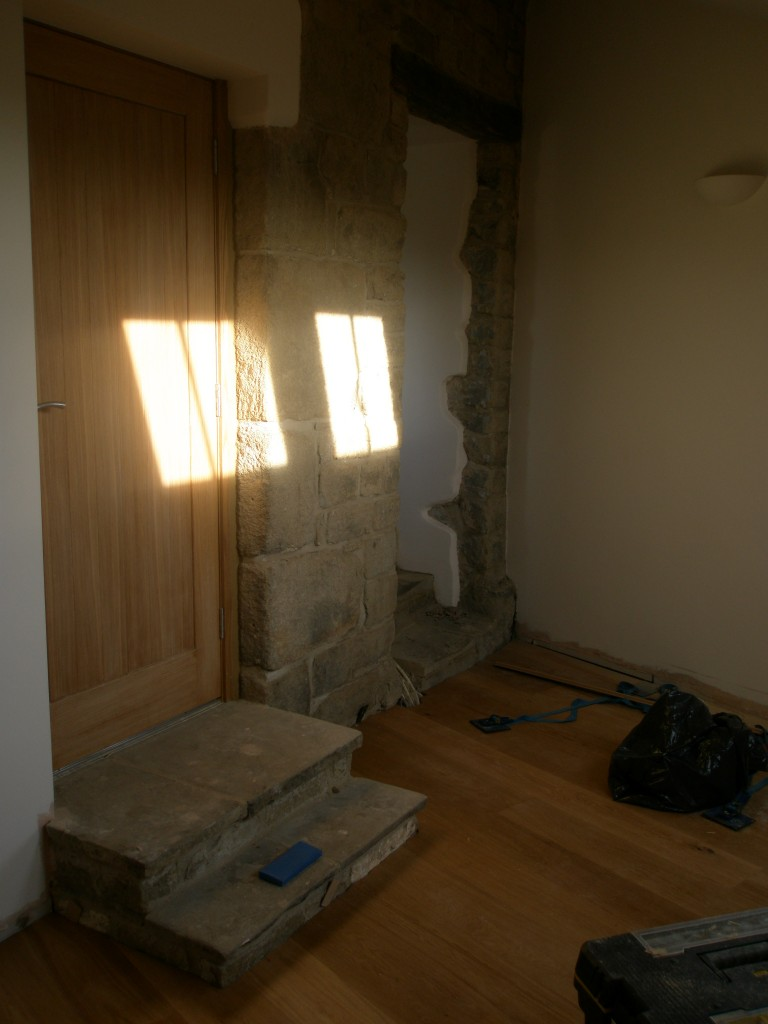 This room used to be the old coal hole. The door to the left leads to the outside.  The steps have been built using flagstones that we reclaimed from the kitchen.  The door to the right leads into the main house and I suspect that this used to be the original door into the property.  It ceased to be used as the front door when the coal hole was built - the coal hole is on the 1768 map, so this doorway pre-dates that - the steps are original (the bottom step forms part of a foundation stone) and show significant signs of wear.