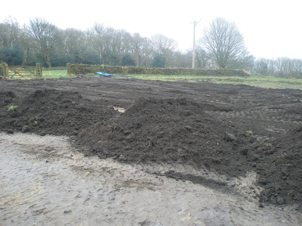 The topsoil is deposited in to heaps across the field.  We then used the digger to level these heaps out.