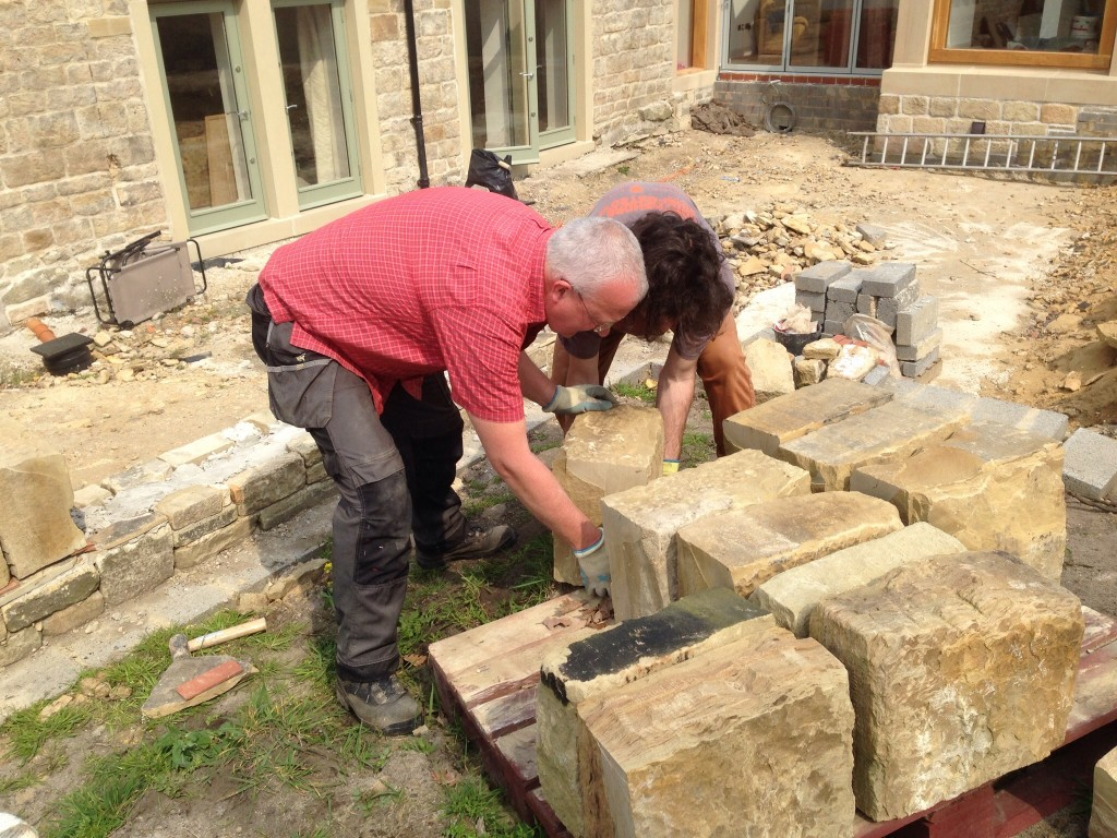 These stones are heavy and often it is difficult to get two sets of hands on them at a time.  This is my and Liam placing one of the topping stones - the sawn side is put to the back of the wall so that it cannot be seen from the sunken garden.