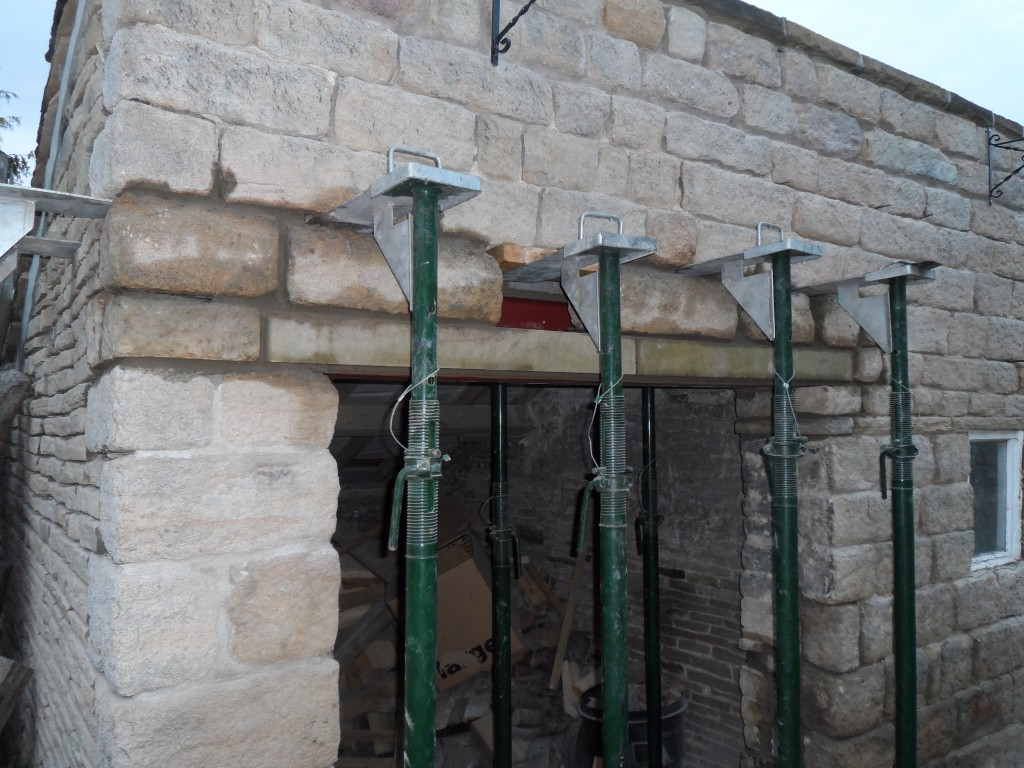 We have used a couple of ashlar lintels that were left over from the house renovation (I think we ordered them by mistake, but no one remembers!).  Anyway, they have been put to good use and now form the course above the door.  This is support behind the steel beam behind.