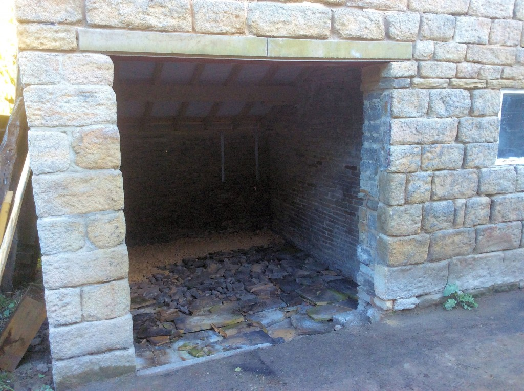 The original floor in the outbuilding sloped to the back.  To correct this, I put some rubble at the back and some old stone slates at the front.  Then covered it with crushed stone which was then compacted.  This corrected the floor level as well as helping raise the finished floor level above the drive outside.