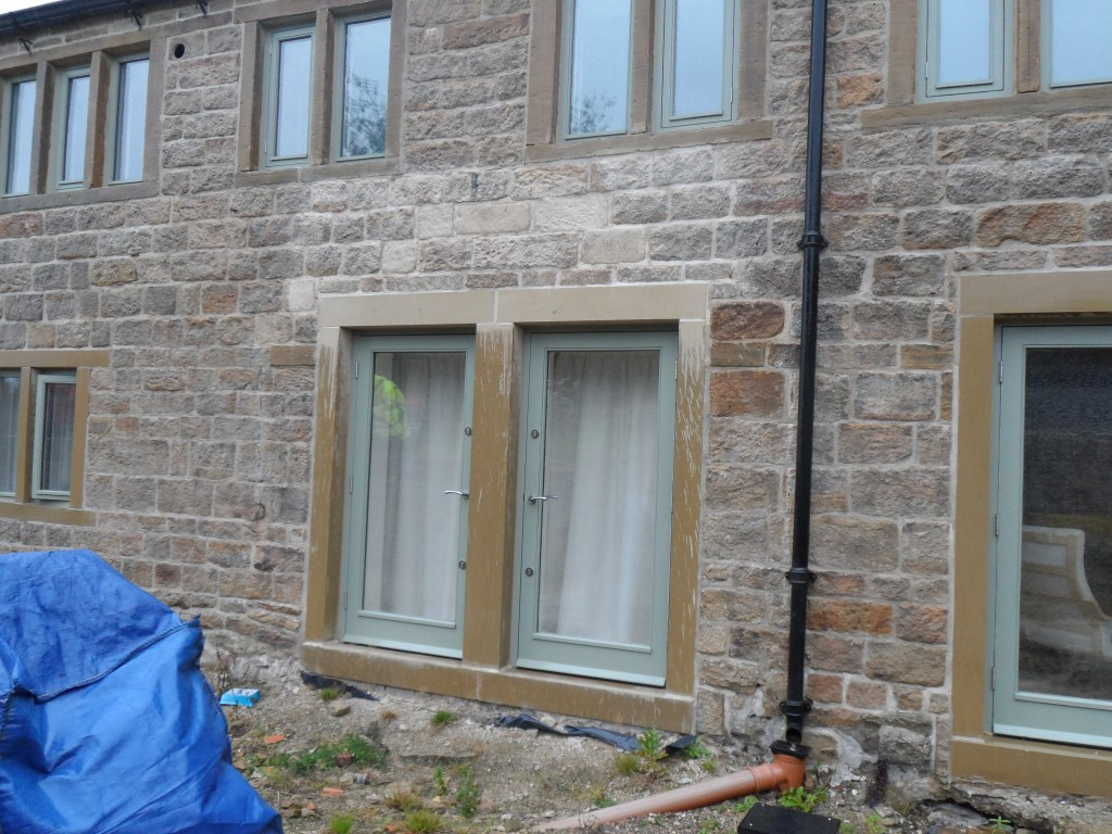 The area above these patio doors was treated with Belzona 5122 in February this year.  Here you can see on a particularly wet October day, the effect that it has had.  Just compare it to the stonework above the patio doors on the right.  You can even see where the Belzona has dripped onto the jambs and the step below.