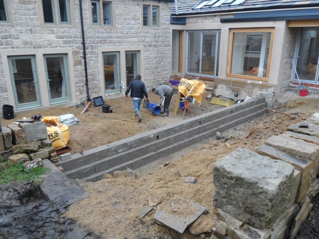 This is the retaining wall that will separate the lower and the upper terrace in the sunken garden.  It has rained throughout the day today and this makes progress slow.  And very muddy!