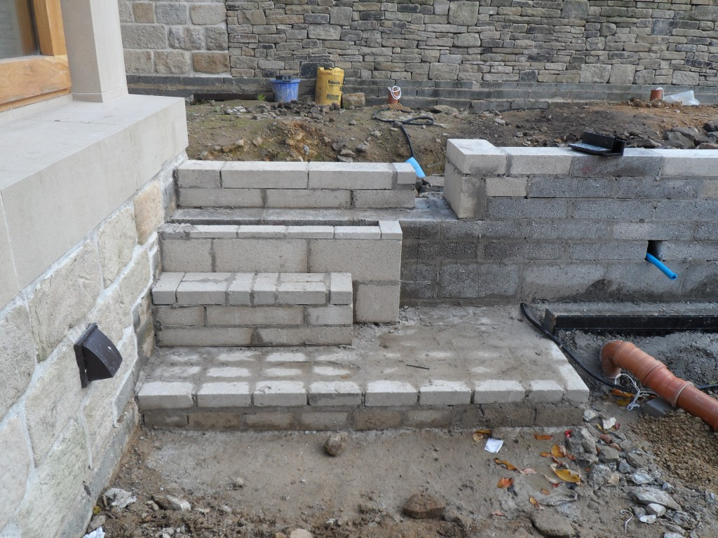 This blockwork has been built to support the stone steps that will be installed here.  The blockwork to the right will be face with the same stone as you can see on the back wall above.
